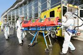 stock photo of ambulance  - HAZMAT medical team pushing stretcher by ambulance on street - JPG