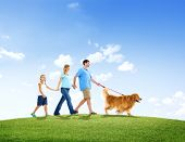 picture of dog-walker  - Family Walking Together with Their Pet Dog Outdoors - JPG