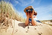 stock photo of dune grass  - Little boy searching with binoculars at the beach dressed as explorer concept for nature - JPG