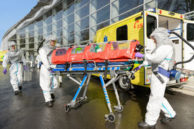 stock photo of ambulance  - HAZMAT medical team pushing stretcher by ambulance on street - JPG