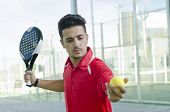 picture of paddling  - Man ready for paddle tennis serve in outdoors court - JPG