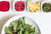 image of pesto sauce  - Arugula salad with pomegranate seeds and sauce pesto sauce and freshly cut avocado in bowls on white background - JPG