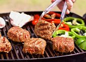 foto of burger  - Australian or american BBQ on a grill with burgers, red pappers and mushrooms ** Note: Shallow depth of field - JPG