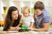 stock photo of boys  - Young happy family with baby boy read children book laying on floor - JPG