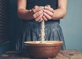 pic of oats  - A young woman is standing with a handful of oats - JPG