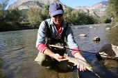 image of fly rod  - Fly fisherman catching a fario trout in river - JPG