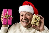 stock photo of gold tooth  - Convivial elderly gentleman showcasing a wrapped present in each hand one gold one pink - JPG