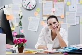 stock photo of boredom  - Tired frustrated female office worker at desk looking at camera - JPG