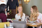 picture of waiter  - Happy young women having meal together at coffeeshop while waiter standing with menu - JPG