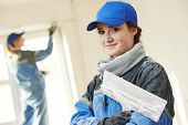 pic of putty  - female plasterer painter portrait at indoor wall renovation decoration stopping with spatula and plaster - JPG