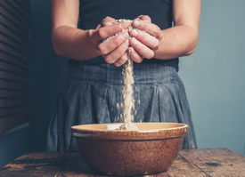 image of oats  - A young woman is standing with a handful of oats - JPG