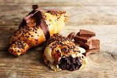 foto of croissant  - Fresh and tasty croissants with chocolate on wooden background - JPG