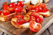 pic of cutting board  - Slices of white toasted bread with canned tomatoes on cutting board on wooden table - JPG