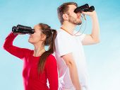 image of lifeguard  - Young man and woman lifeguards on duty or tourist couple looking through binocular studio shot on blue - JPG