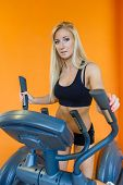 image of elliptical  - Young sports woman doing exercises on an elliptical trainer in the gym - JPG