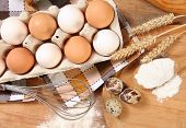 foto of chicken-wire  - Eggs and wheat on wooden table - JPG