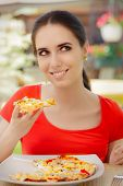 stock photo of table manners  - Beautiful girl eating pizza in a restaurant  - JPG