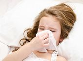 pic of blowing nose  - Sick little girl lying in the bed and blowing her nose - JPG