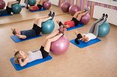 stock photo of crunch  - Young fit people doing crunches with fitness ball - JPG