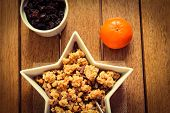 stock photo of satsuma  - A bowl of healthy granola with a fresh orange and dried fruit - JPG