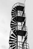 image of fragmentation  - Abstract architecture fragment old outdoor metal spiral ladder on the wall black and white photo - JPG
