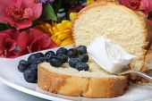 stock photo of pound cake  - Slice of pound cake with blueberries and spoon topped with whipped cream and flowers in the background - JPG