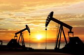 pic of smog  - silhouette of working oil pumps on sunset background - JPG