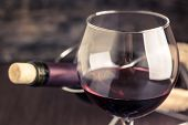 picture of merlot  - Red wine in wineglass against corked bottle on wood background - JPG