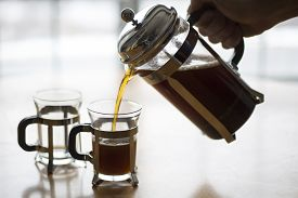 stock photo of coffee grounds  - A back lit image of coffee being poured into small coffee mugs from a French Press with the light source being a window behind the table - JPG