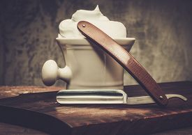 foto of razor  - Shaving bowl and straight razor on wooden background  - JPG