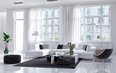 image of monochromatic  - Modern spacious airy living room interior with white and black decor with an upholstered suite below large windows giving a view of an apartment block - JPG