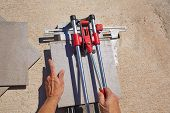 pic of mason  - tile cutter machine with mason hands cutting tiles - JPG