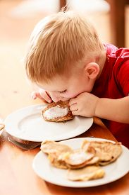 pic of icing  - Little funny boy eating with relish mael fried apple in pancake dough or apple fritters pancakes with icing sugar at home - JPG