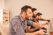 Side View Of Three Friends Playing Video Games At Home poster