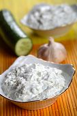 stock photo of chafing  - Yogurt dressing with chafed cucumber and clove of garlic  - JPG