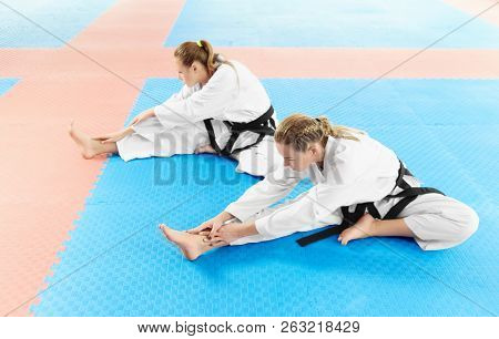 poster of Two Girl Wearing In White Kimono And Black Belts, Training Their Flexibility Before Training In Figh