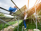 Solar Photo Voltaic Panel System Installing. Two Technicians Standing On Ladder And Platform Top Mou poster