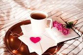 Cup Of Tea Staying On Open Book With Flowers And Lights At Background. Valentines Day. Good Morning. poster