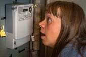 Terrified Woman Is Checking Electricity Meter - Consumption And Expensive Electricity Concept poster