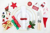 Christmas dinner fun table setting with porcelain plates, bauble decorations, cutlery, gift box, nap poster