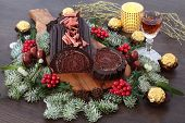 Yule chocolate decorated log cake for the christmas season with winter flora, alcoholic drink and fo poster
