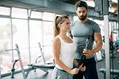 Personal Trainer Assisting Beautiful Woman Lose Weight poster