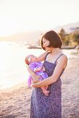 Mother Holds Little Girl On Sea Beach. Baby Is In Lilac And Lavender Dress. Infant Look At Woman. Co poster