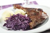Roasted goose leg with potato dumplings and braised cabbage