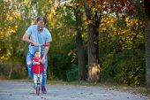 Father Riding With His Toddler Son  Scooter In A Autumn Park. . Active Family Leisure. Sports, Leisu poster