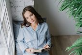 Top View Of Relaxed Pleasant Looking Woman Enjoys Reading Book, Dressed In Casual Domestic Suit, Sit poster