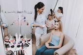 Blond Girl In Beauty Salon. Makeup In Beauty Salon. Makeup Artist Puts Powder. Woman And Makeup Arti poster