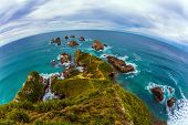 Travel to New Zealand. Nuggets Point is a landmark relief on the Otago coast, surrounded by rocky is poster