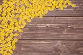 Lot Of Whole Raw Yellow Pasta Conchiglie Variety Right Upper Corner Flatlay On Brown Wood poster