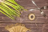 Set Of Lot Of Whole Fresh Green Asparagus Spear With Jute Spool Flatlay On Brown Wood poster